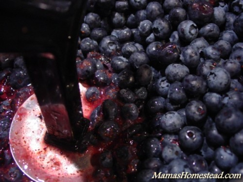 Smashing blueberries for jam